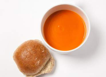A bowl of soup and a roll.